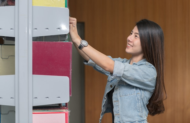 Cute asian woman selecting book from a bookshelf in library, learning and education concept