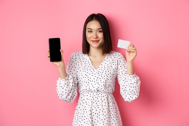 かわいいアジアの女性がオンラインで買い物をし、銀行のクレジットカードとモバイル画面を表示し、笑顔でカメラを見て、ピンクの上に立っています。