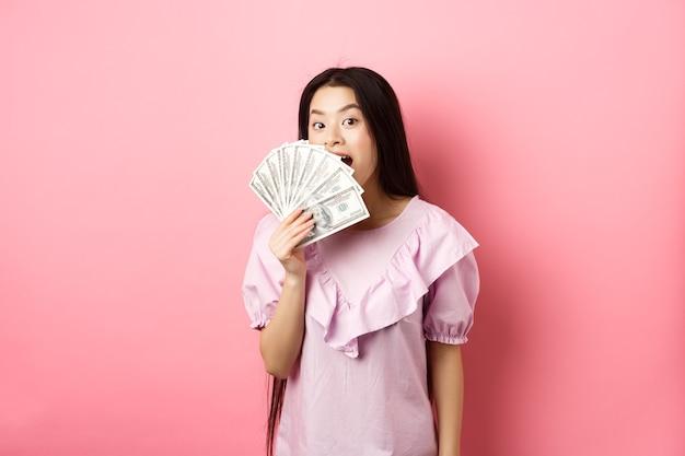 ドル札を見せて、驚いて微笑んでいるかわいいアジアの女性。ピンクの背景に立って、お金で放棄する金持ちの女性。
