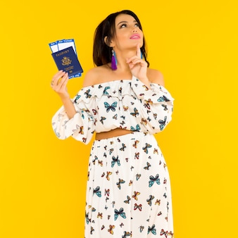 A cute asian woman in a silk dress with butterflies is holding a passport and air tickets