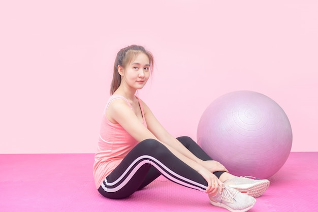 Cute asian woman smile with balls on pink background.