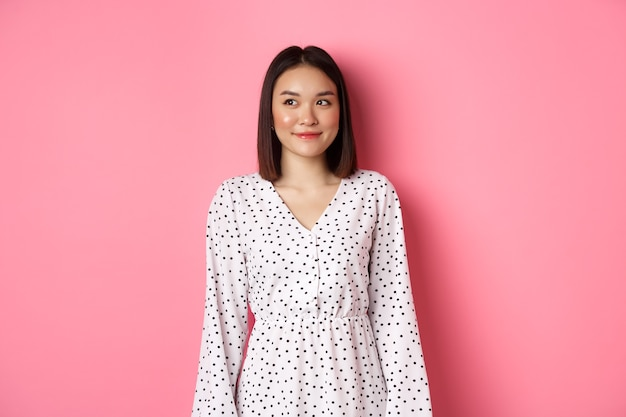 Cute asian woman smiling, looking left at copy space, standing on romantic pink background