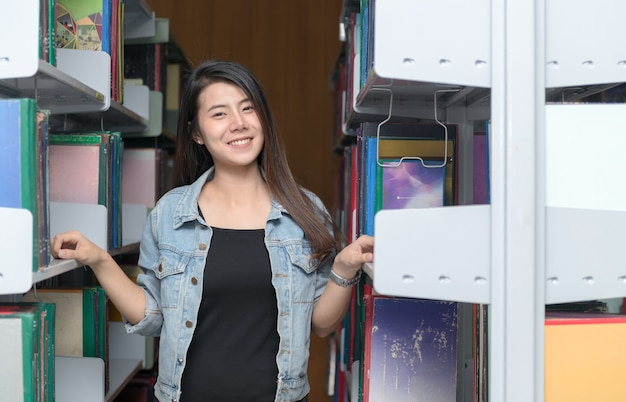 Cute asian woman student smile with bookshelf in library, learning and education concept