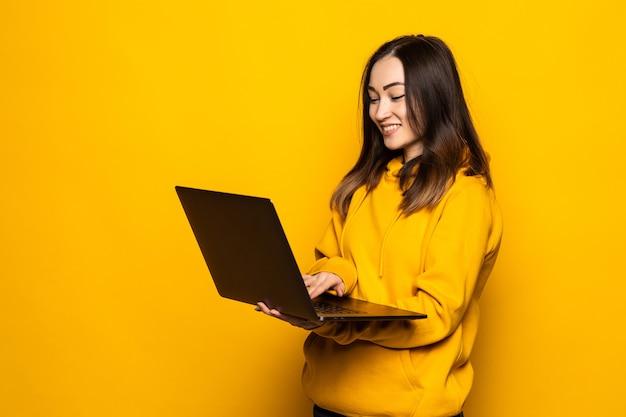 Carina donna asiatica che studia sul computer portatile e sorride, in piedi contro il muro giallo