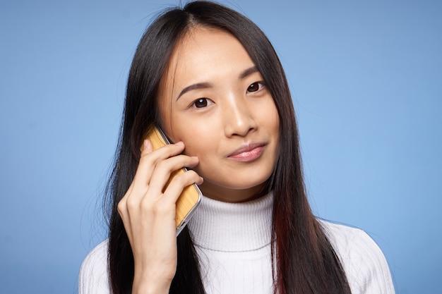 Милая азиатская женщина разговаривает по телефону технологии синего.