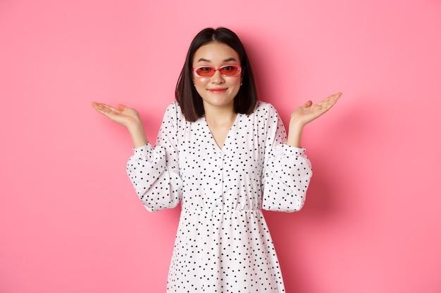 Симпатичная азиатская туристка улыбается в камеру, невежественно пожимая плечами, не знаю, в модных солнцезащитных очках и белом платье, противостоит розовому.