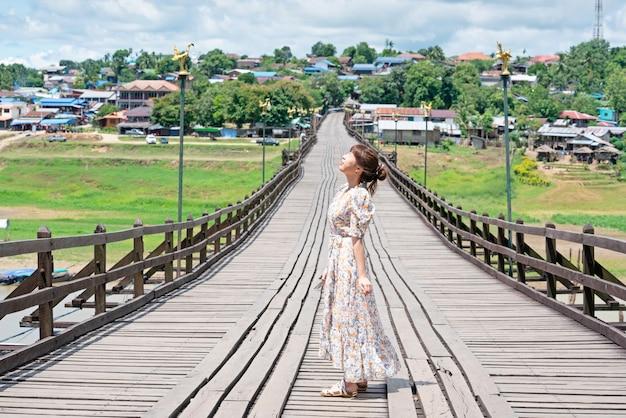 Cute asian woman wear casual posting alone on wooden bridge at sangkhaburi, kanchanaburi, thailand.