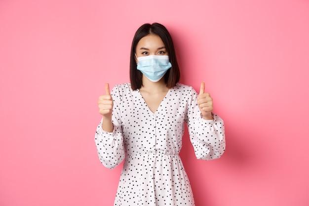 의료 마스크와 드레스를 입고 귀여운 아시아 여자