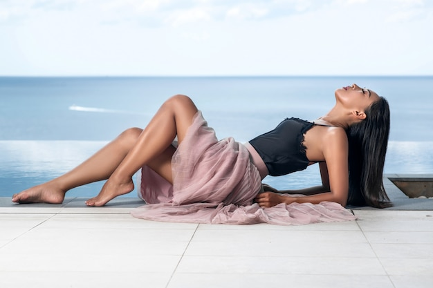 A cute asian woman with beautiful slim legs and closed eyes poses on the edge of the infinity pool. fashionable advertising photo