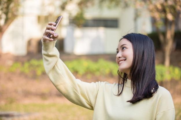 かわいいアジアの女性は自分の携帯電話を使って自撮りを撮り、自宅の庭で幸せな笑顔を見せています。