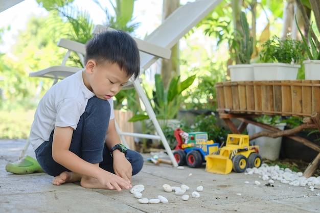 家で小石やおもちゃの建設機械で遊ぶかわいいアジアの幼稚園の少年
