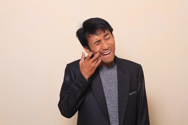 Cute asian young man with painful checking between his teeth, wearing a suit with a sweate