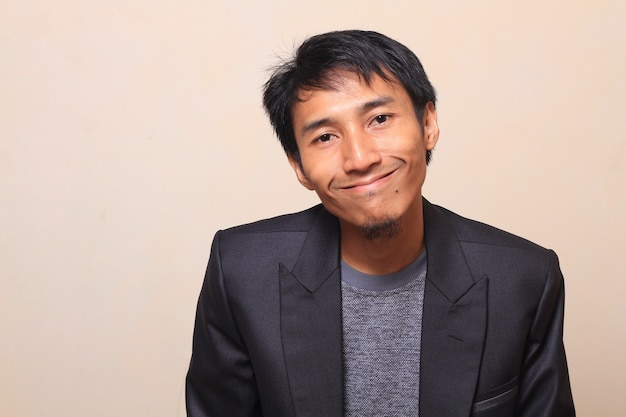 Cute asian young man with smile face and happy expression, wearing a suit with a sweater i