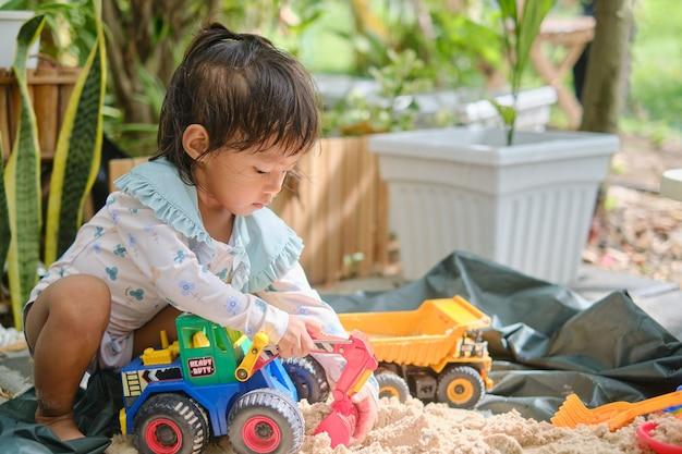 집에서 혼자 모래와 장난감 건설 기계를 가지고 노는 귀여운 아시아 어린 소녀