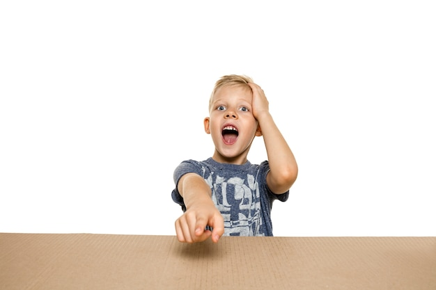 Cute, astonished little boy opening the biggest postal package.