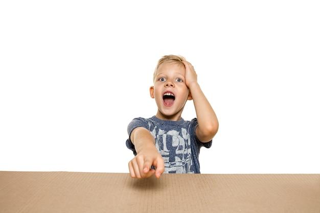 가장 큰 우편 소포를 여는 귀엽고 놀란 어린 소년.