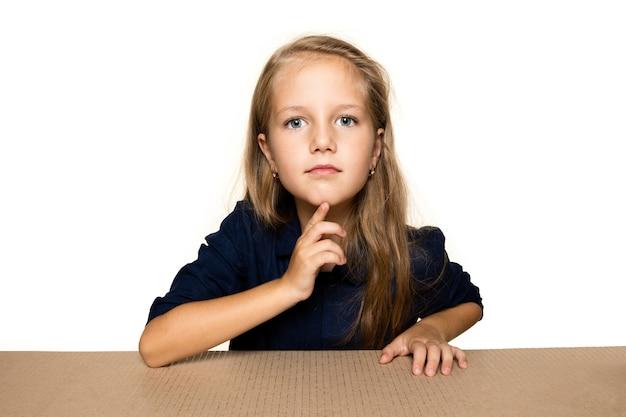 Bambina sveglia e stupita sul pacco postale più grande. eccitato giovane modello femminile in cima alla scatola di cartone guardando dentro.