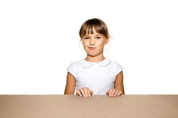 Bambina sveglia e stupita che apre il pacco postale più grande. eccitato giovane modello femminile in cima alla scatola di cartone guardando dentro.