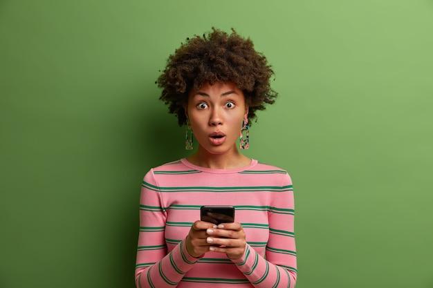La donna carina e stupita usa l'applicazione online, usa il cellulare per chattare nei social network, sbalordita nel leggere notizie sorprendenti, scioccata dal messaggio ricevuto, si trova al coperto. concetto di tecnologia