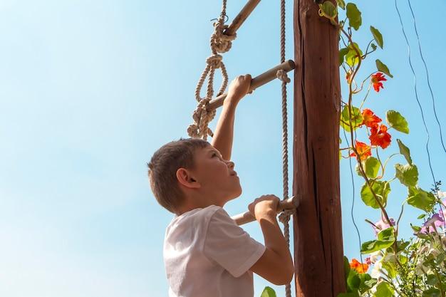높은 밧줄 사다리에 등반 귀여운 운동 작은 소년 아이. 아이들을 위한 놀이공원. 어린이를 위한 야외 활동 및 게임. 웨이 업 컨셉