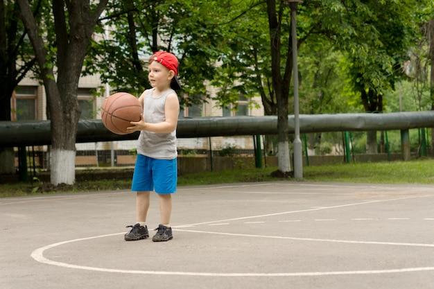 バスケットボールをしているかわいい運動少年