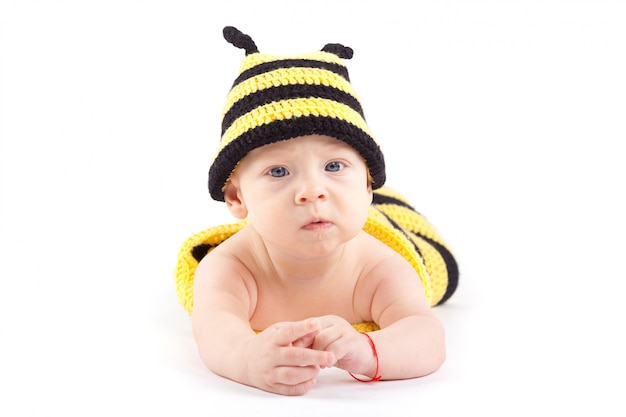 Cute attractive baby boy in bee costume lies on tummy