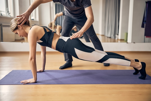 Cute attractive blond with fit body working out in yoga class while experienced instructor showing her correct pose