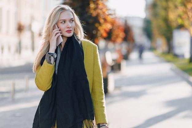 晴れた日に路上のパッケージでかわいい魅力的なブロンドの女性。ショッピングの後の電話でのコミュニケーション、前向きな感情。