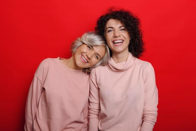 금발 머리를 가진 그녀의 가장 친한 친구가 빨간 벽에 분홍색 옷을 입고 웃고 그녀의 어깨에 머리를 기울고있는 동안 웃고 귀여운 매력적인 곱슬 여자.