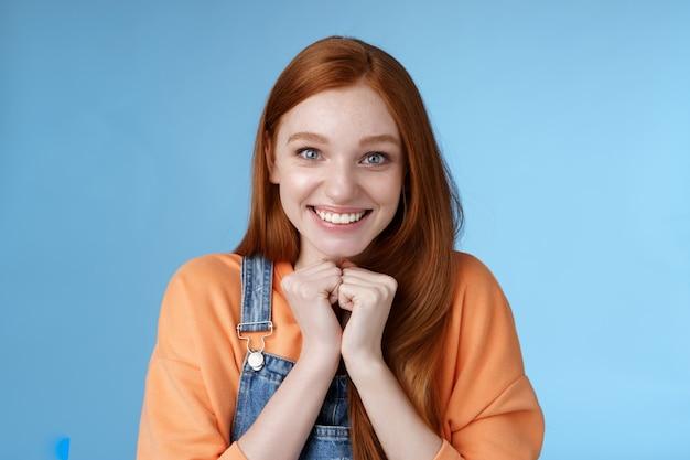 Симпатичная привлекательная взволнованная улыбающаяся счастливая рыжая девушка с голубыми глазами и веснушками получает отличную возможность учиться за границей, улыбаясь, радуясь, очень благодарно смотреть, благодарная удивленная камера, синий фон.