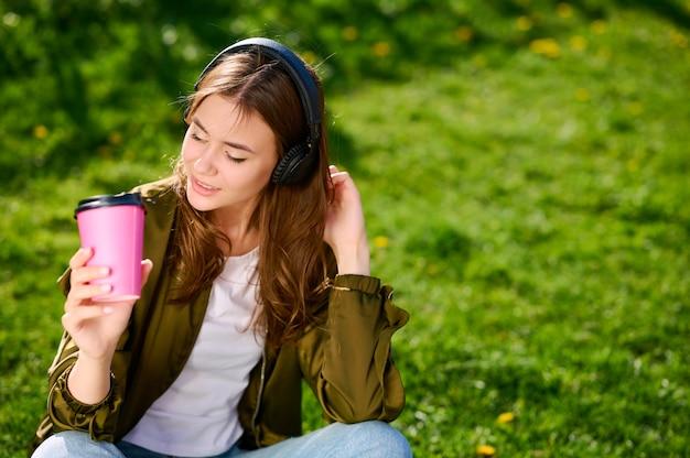 屋外の公園の芝生の上にリラックスして座って、ヘッドフォンで音楽を聴くかわいい魅力的な女子学生(女性)