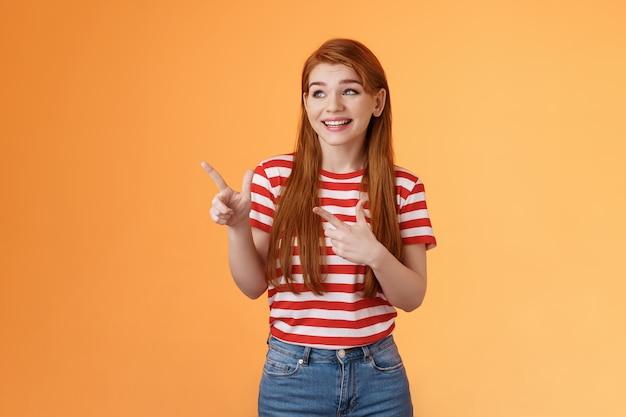 可愛くて魅力的なフェミニンな生姜の若い女性が大まかにポインティングして笑って、幸せに反応して左に見えます...