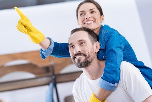 手袋を着用してニヤリと掃除しながらいちゃつくかわいい魅力的な面白いカップル