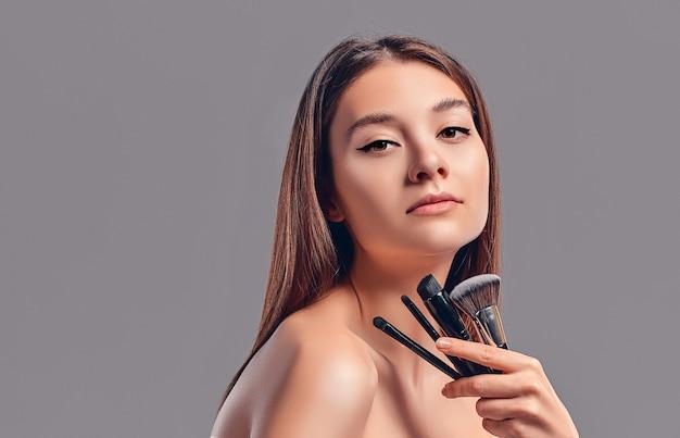 회색 배경에 고립 된 메이크업 브러쉬를 들고 귀여운 매력적인 소녀. 피부 관리 개념입니다. 스파 트리트먼트, 미용, 메이크업.