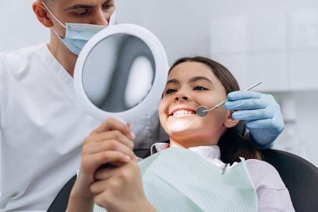 거울을 들고 치과를 방문하는 귀여운 매력적인 소녀 의사는 환자의 치아를 검사합니다