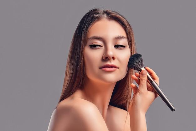 Милая привлекательная девушка с полотенцем использует кисть для пудры или румян, изолированных на сером фоне. концепция ухода за кожей. санаторно-курортные процедуры, косметология, макияж.