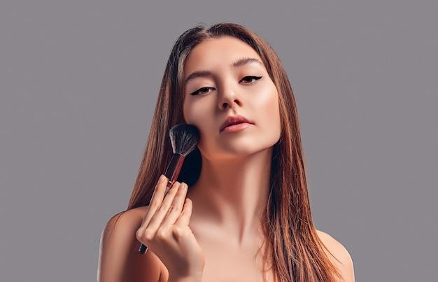 Милая привлекательная девушка с полотенцем использует кисть для пудры или румян, изолированных на сером фоне. концепция ухода за кожей.
