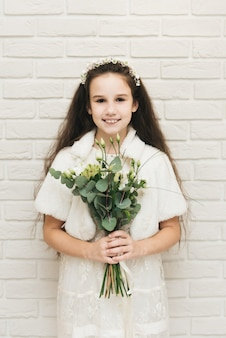 Cute attractive girl with a bouquet of flowers in her hands on a white wall