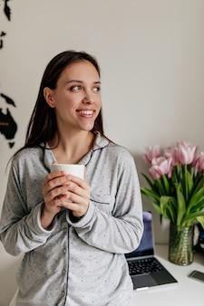 長い黒髪と素敵な笑顔のかわいい魅力的な女の子が家のパジャマを着てコーヒーを押しながらモダンなアパートの窓を見ています。