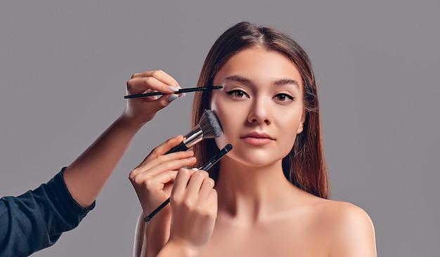 Милая привлекательная девушка с кистями для макияжа, изолированными на сером фоне. салон красоты, макияж.