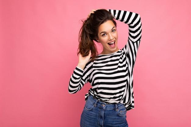かわいい魅力的なかなり幸せな笑顔素晴らしい若いブルネットの女性はカジュアルを着ています