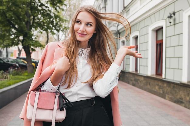 Симпатичная привлекательная стильная улыбающаяся женщина гуляет по городской улице в розовом пальто весенней модной тенденции, держащей кошелек, элегантный стиль