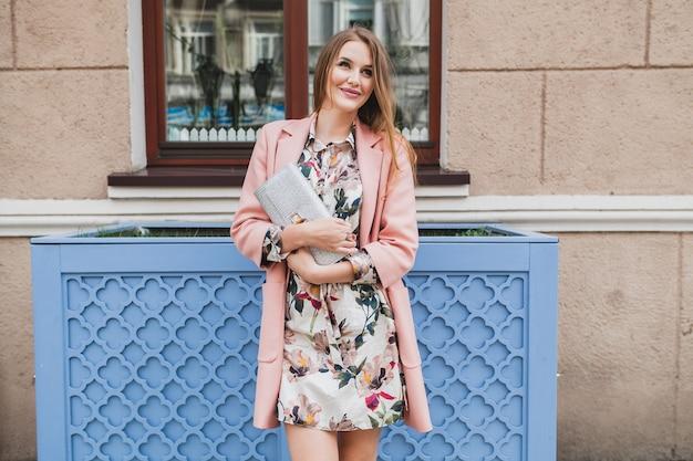 イヤホンで音楽を聞いて、財布を持ってピンクのコート春のファッショントレンドの街を歩いているかわいい魅力的なスタイリッシュな笑顔の女性