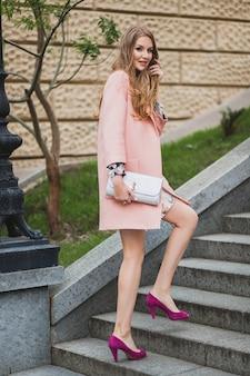 ピンクのコート春のファッショントレンドの財布を保持して街を歩いてかわいい魅力的なスタイリッシュな笑顔の女性