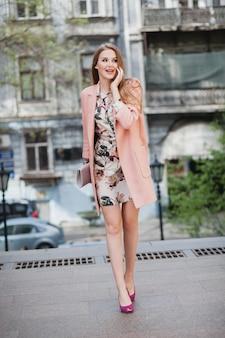 ピンクのコートで街を歩くかわいい魅力的なスタイリッシュな笑顔の女性