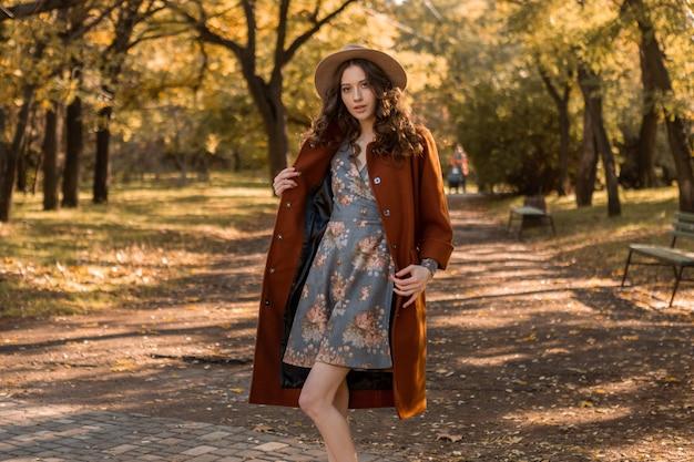 プリントドレスと暖かいコートを着て公園を歩く巻き毛のかわいい魅力的なスタイリッシュな笑顔の女性秋の流行のファッション、ストリートスタイル