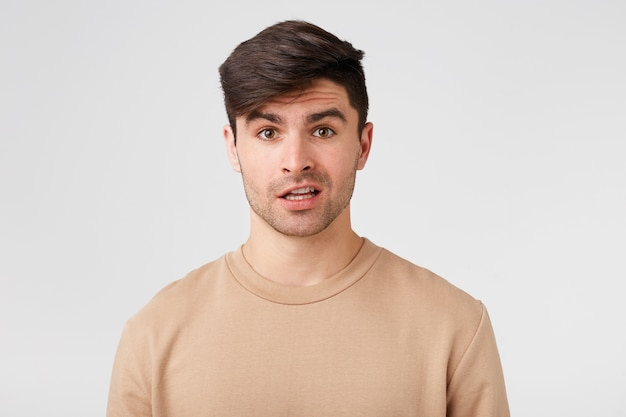 Cute, attractive, unshaven man looks confused, with an uncomprehending expression