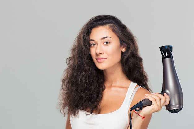 Cute attractive woman holding hairdrye