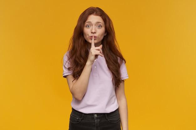긴 생강 머리를 가진 귀엽고 매력적인 여자. 분홍색 티셔츠를 입고. 사람과 감정 개념. 침묵의 표시를 보여주고 조용히 해달라고 요청합니다. 오렌지 벽 위에 절연