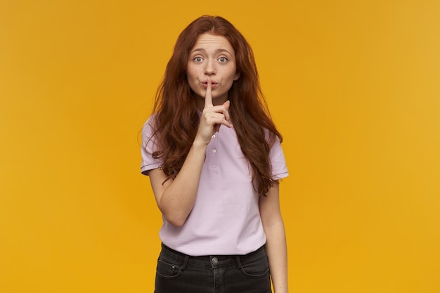 Cute, attractive woman with long ginger hair. wearing pink t-shirt. people and emotion concept. showing silence sign, asks to be quiet.  isolated over orange wall